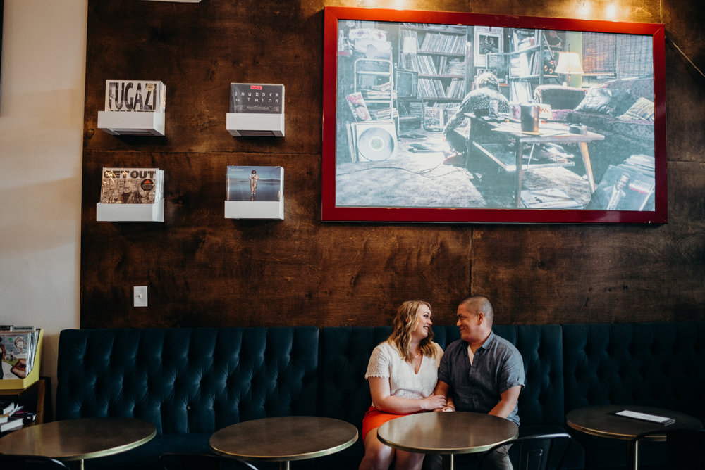 engaged couple sitting in cafe at Songbyrd Cafe and Record Store with art and records behind them