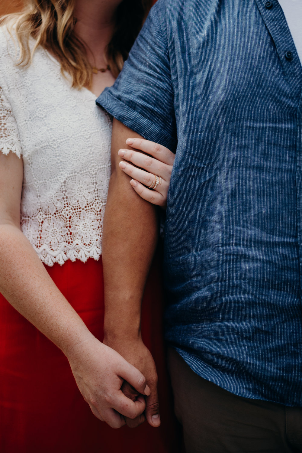 closeup of engaged couple holding hands