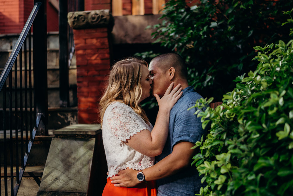 engaged couple kissing in front of brick building in Washington DC neighborhood