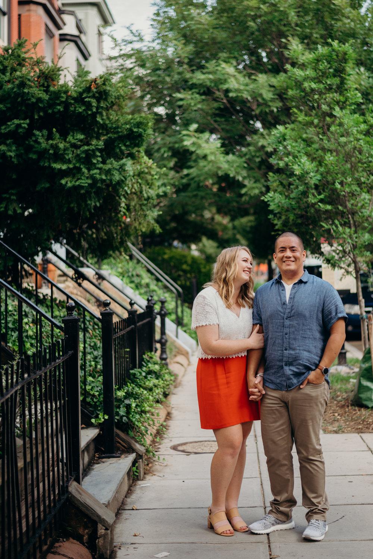 engaged couple posing on sidewalk of Washington, D.C. neighborhood