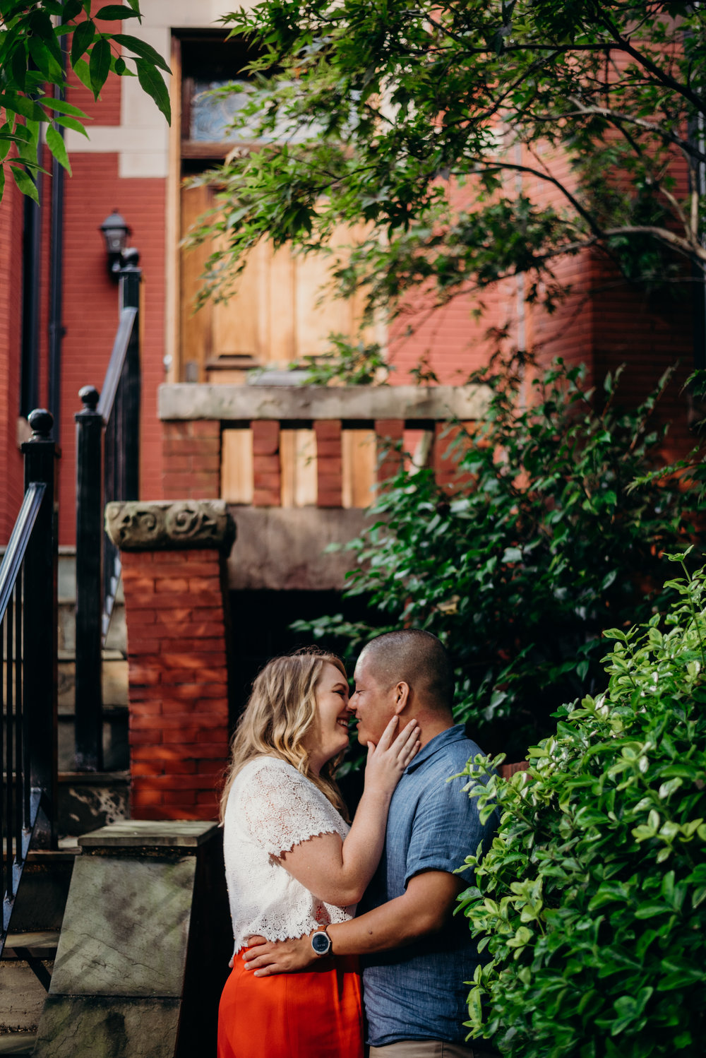 engaged couple kiss with brick building and trees in background
