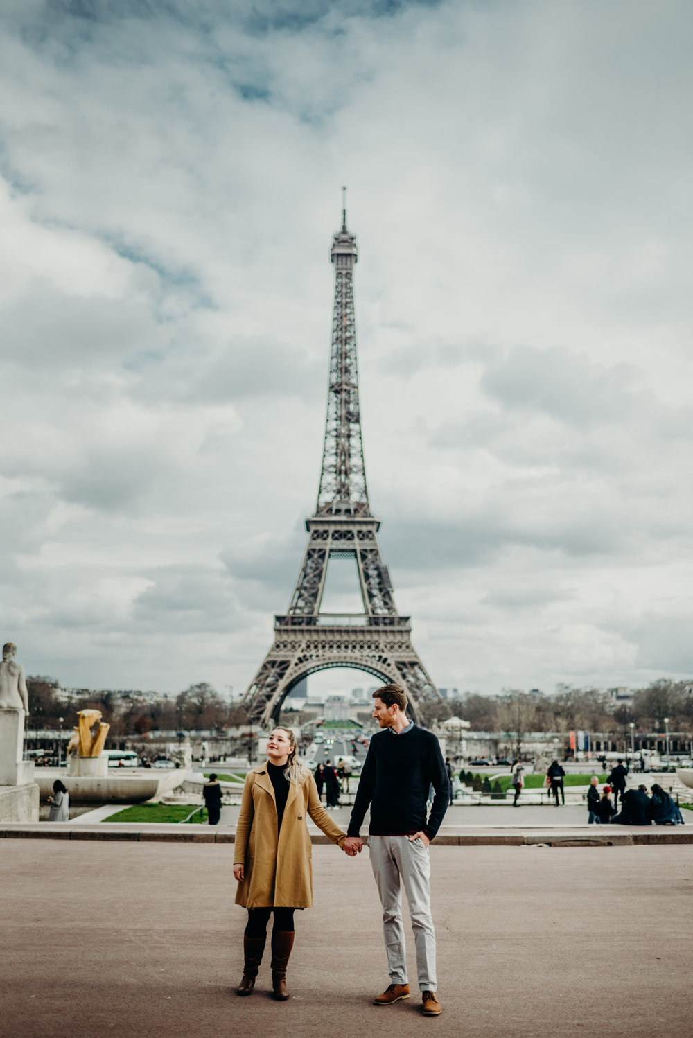 newlyweds on their honeymoon posing in front of the Eiffel Tower in Paris, France