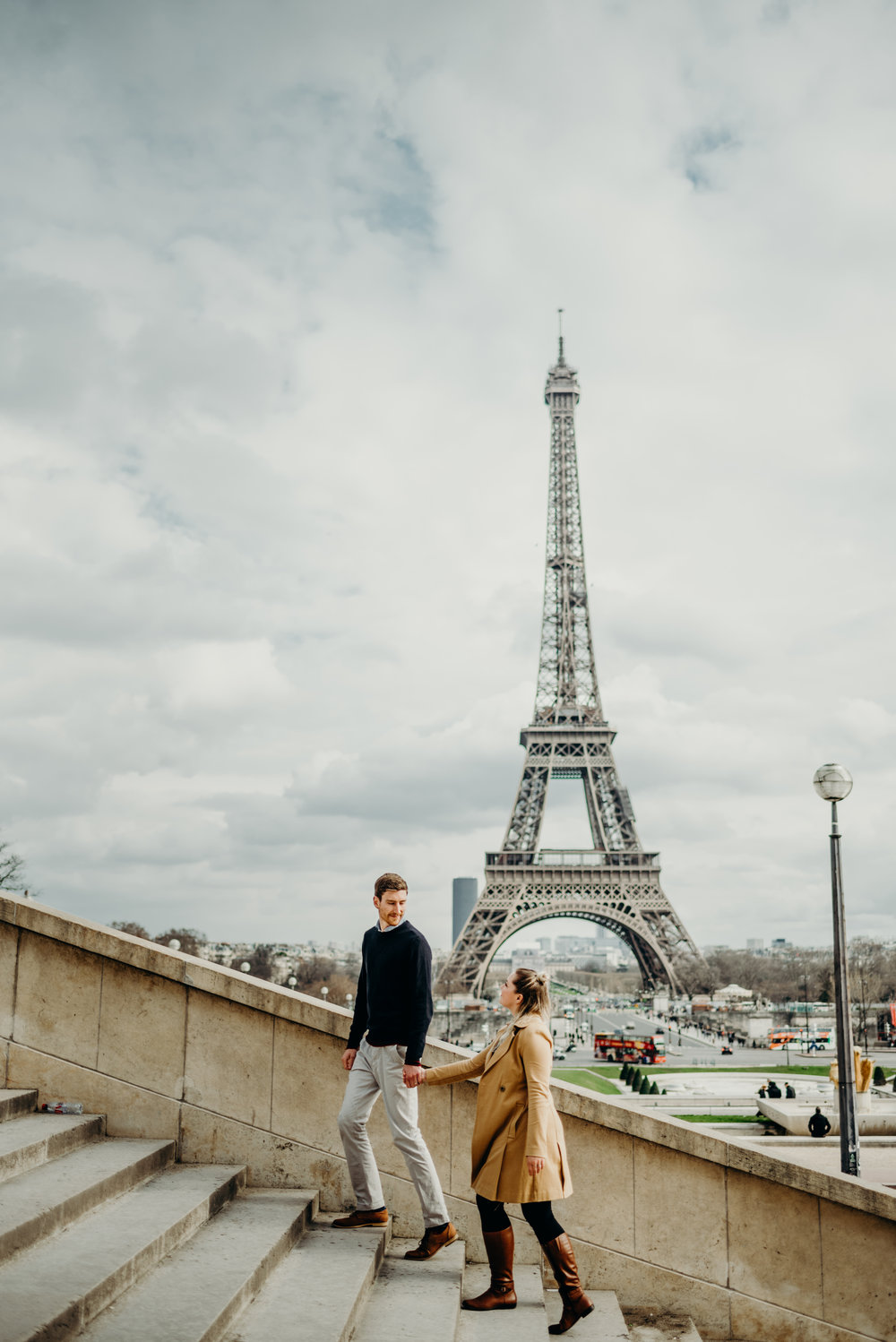 newlyweds climbing stairs in Paris with Eiffel Tower in the background