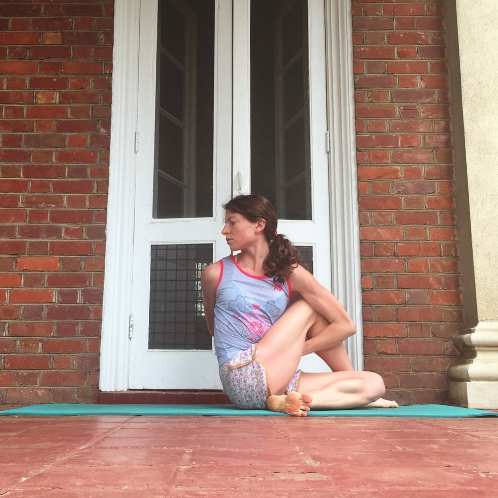 6. HALF LORD OF THE FISHES POSE.    From pigeon, roll to your outer hip. Use your closer hand to gather up back leg--cross foot of this leg over your front knee. Be sure both hips are planted down. Twist towards the side of your top leg. Bind or just use your elbow to help the twist.