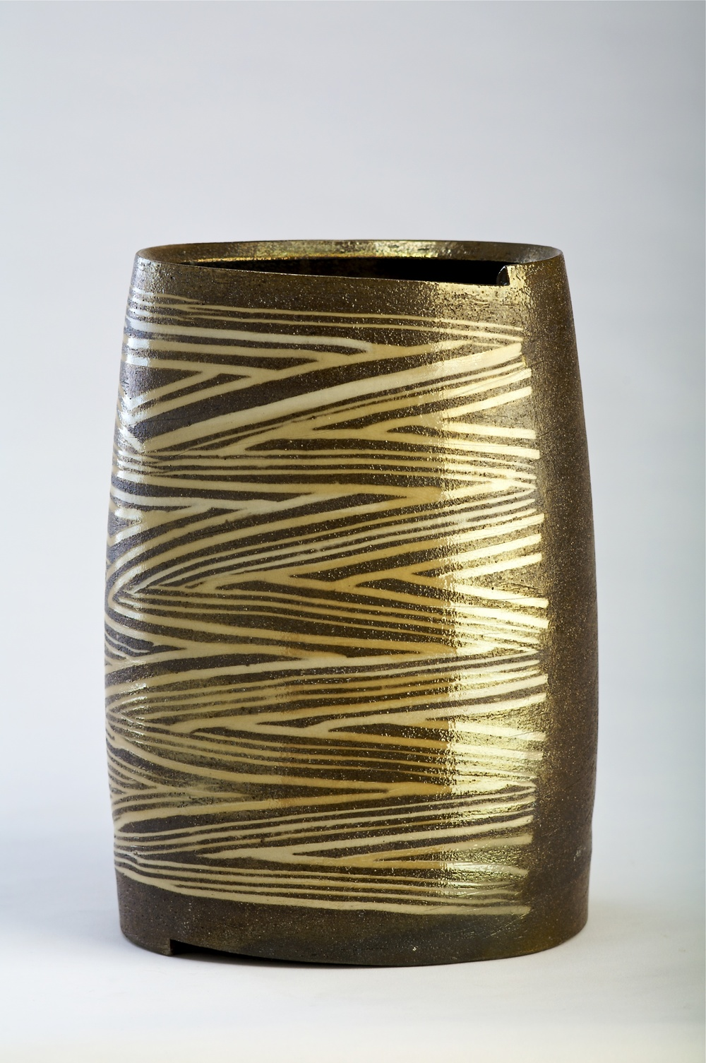 Thrown altered and cut ovoid form.  incised pattern with Inlaid slip.  Sagger fired with charcoal and granite luster glaze  350mm H  2009