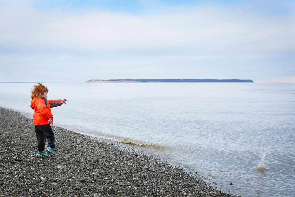 "As this child throws rocks into the water, his mom tells me: ""It's the simple things."""