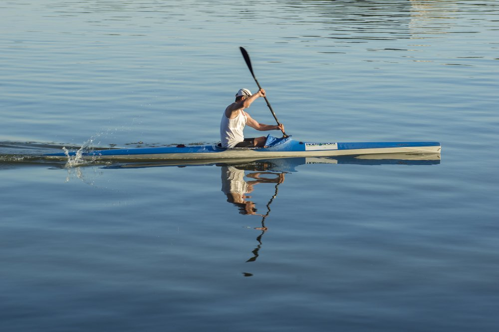Man kayaking in still water with reflection