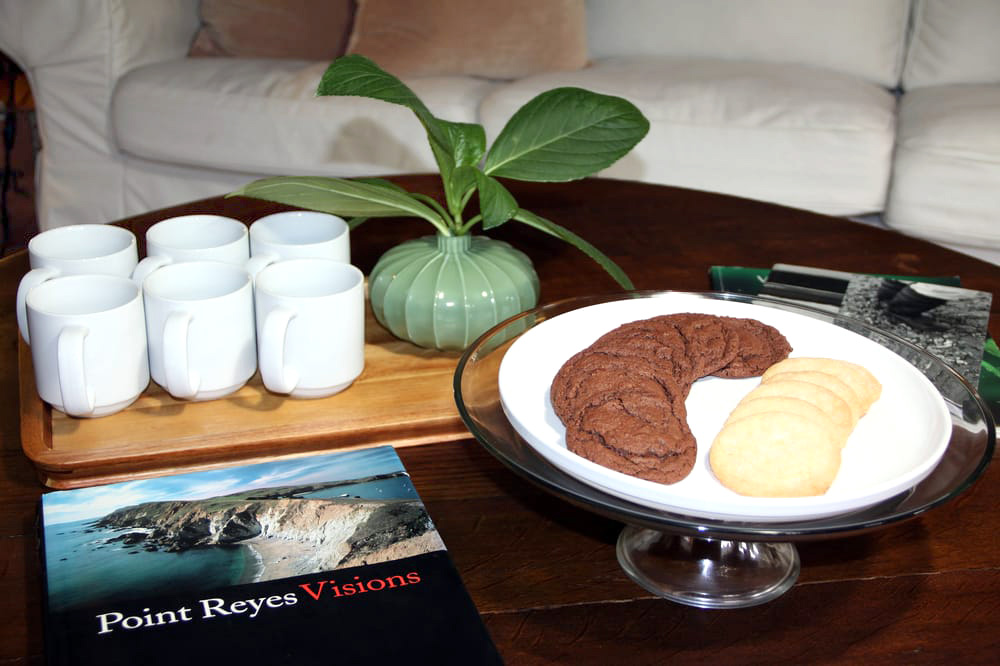 Fresh baked cookies, green plant, and Point Reyes photography book on a coffee table in the living room