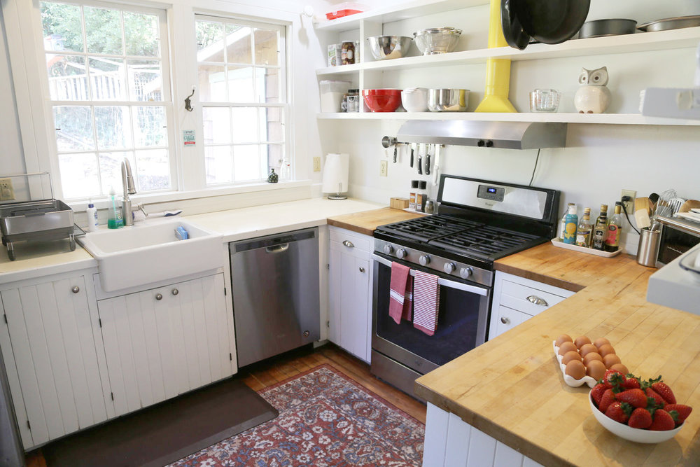 Bright white kitchen with open shelving, wood countertops, and farm sink