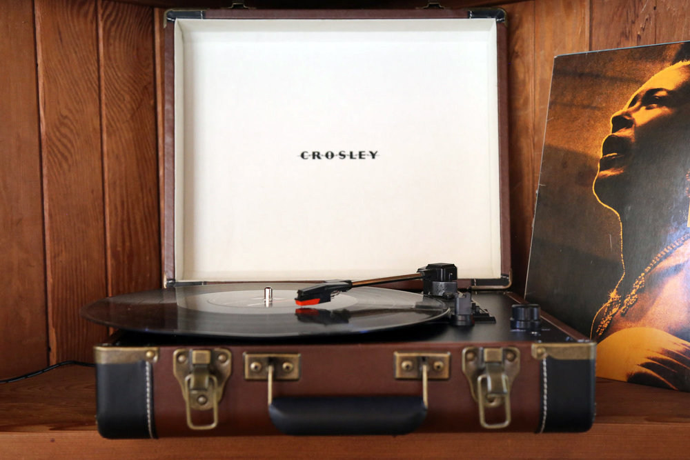 Crosley vintage record player with vintage record against wood paneling