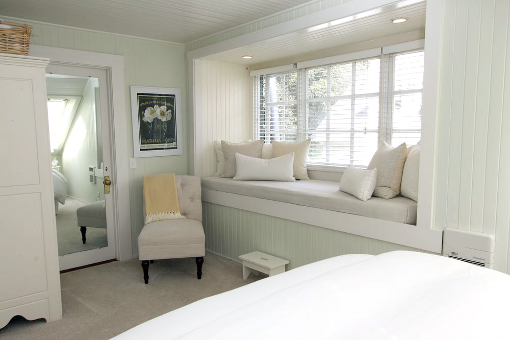 Window seating with recessed lighting in a bright bedroom