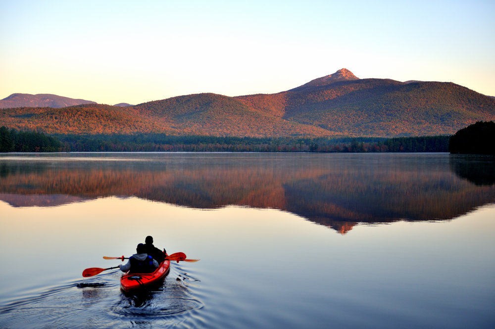 Double kayak in still water with mountains in the background