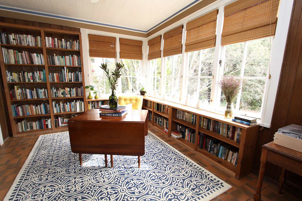 Built in book cases by a brightly lit corner window with a flower arrangements on a vintage desk