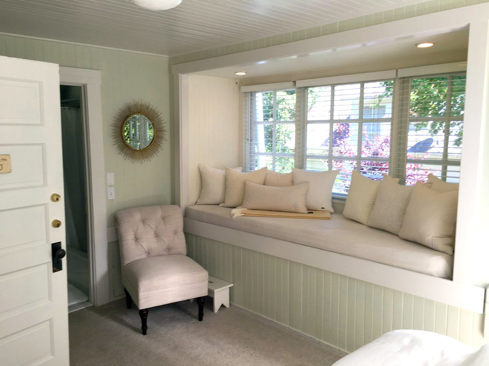 Window seating with white pillows and recessed lighting