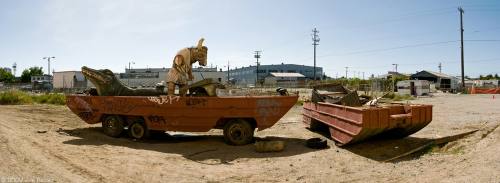 An alligator and a minotaur take a ride in an amphibious vehicle -- by Joe Reifer