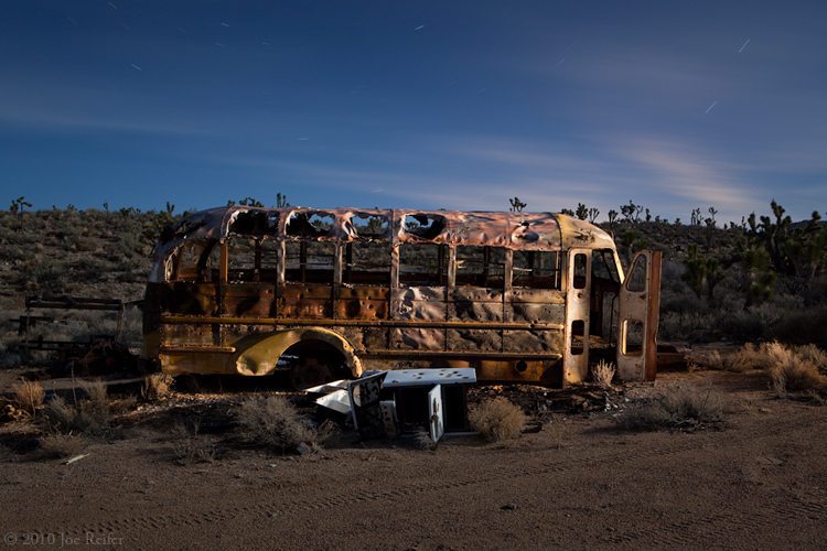 Burned school bus, abandoned desert mining area -- by Joe Reifer