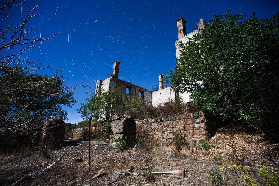 Resort stone ruins at night: Three chimneys in the trees -- by Joe Reifer