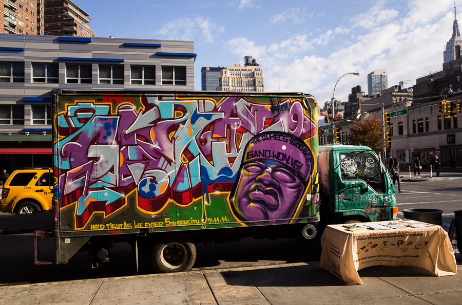 Compost truck graffiti ignored by passers by as famous buildings loom.
