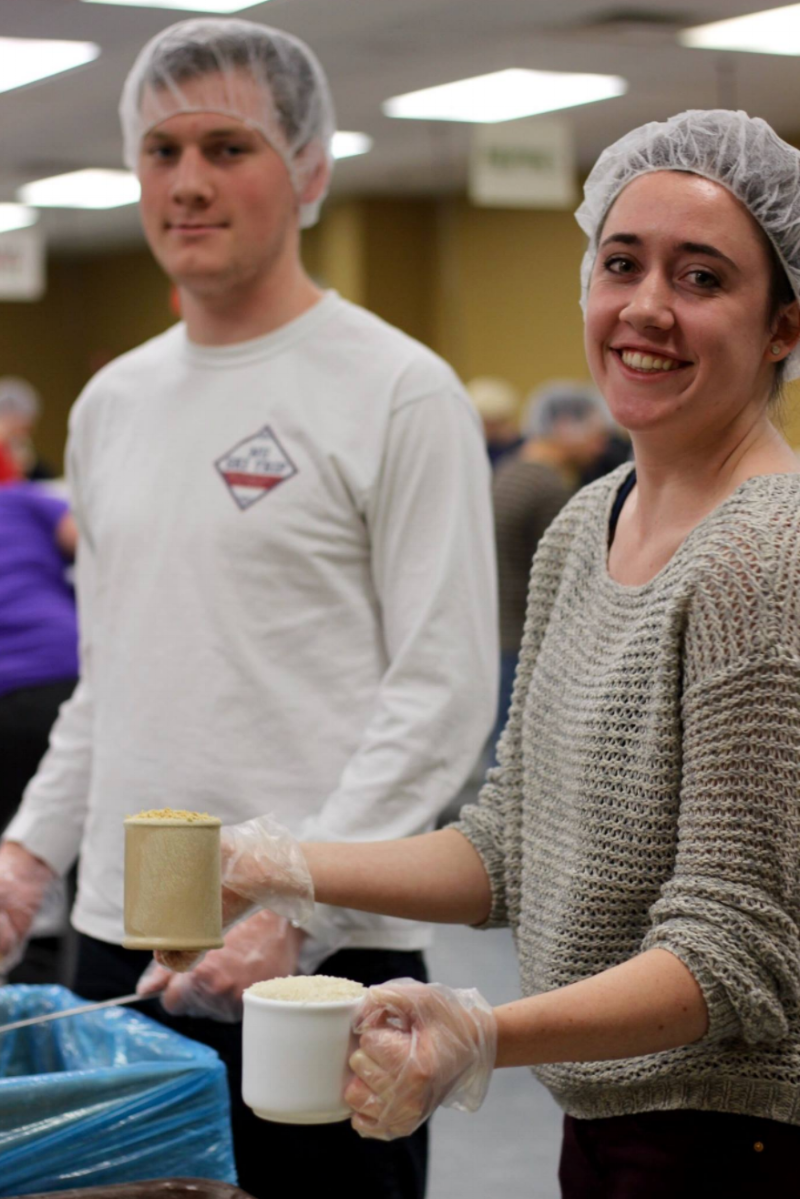 Joe Blackman (Beta Theta Pi PC '15) and Ava Armacost (Gamma Phi Beta PC '16) channel their inner lunch ladies at Feed My Starving Children