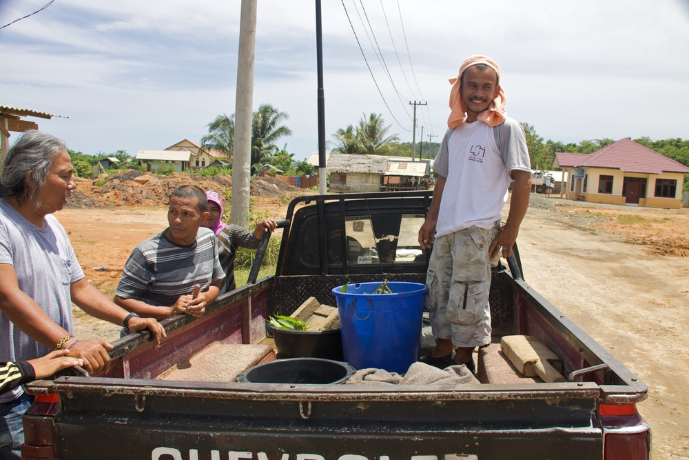 """I've used the USAID road,"" Hasbi says, ""if I have to go to Banda Aceh, I've used the USAID road. But I'd rather use the government [old] road. If we use the USAID road and we don't have the tax sticker on the motorbike, we'll get arrested. If you get arrested, the fine is a hundred and fifty thousand (rupiah, approximately $15 USD)."" A farmer like Hasbi, if caught without the tax sticker, would likely not be able to pay the fine. Rules such as this one have limited the usefulness of the road for poorer Acehnese. A husband and wife pull up outside the road office in their old Chevy pickup truck. The man is a local subsistence farmer, and is selling plants, clams and eels. He thinks his life has improved since the creation of the new road. He says he only needs to pay a police tax now when traveling, instead of one to the GAM (Free Aceh Movement) and one to the military."