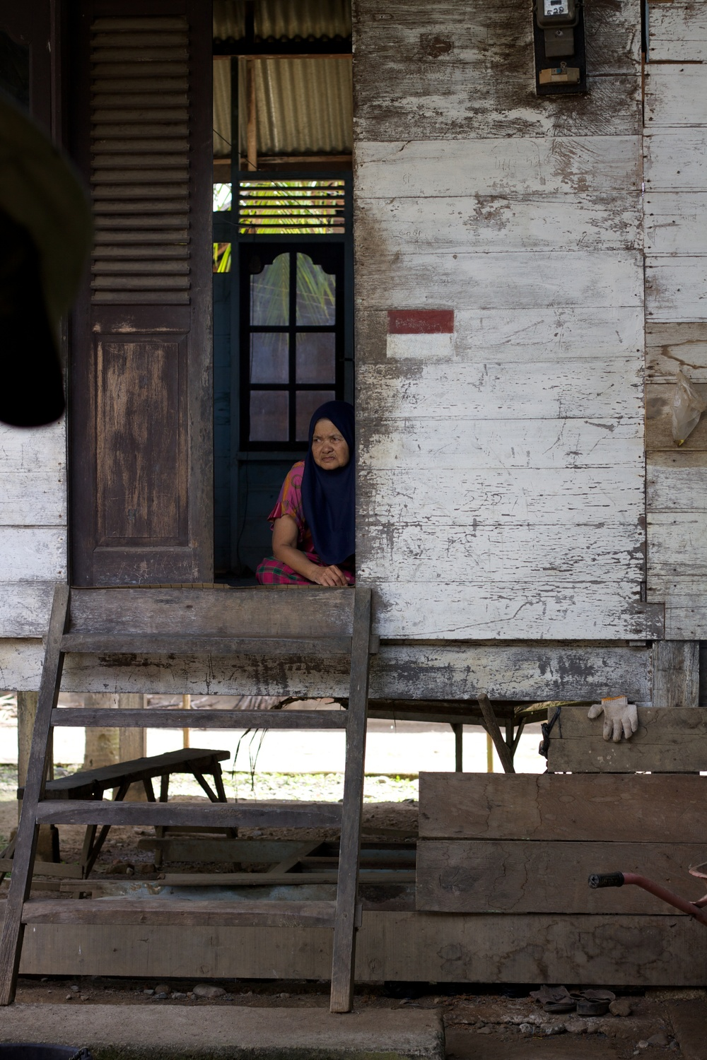 "A woman in a village near the USAID road in Aceh, Indonesia rests in the doorway of an old wooden house, even though her family did receive a new ""World Vision House"" as part of the post-tsunami aid efforts of 2004. If possible, the villagers try to take their afternoon naps in any surviving wood structures, as they are much cooler than the aid-built concrete houses with metal roofs."