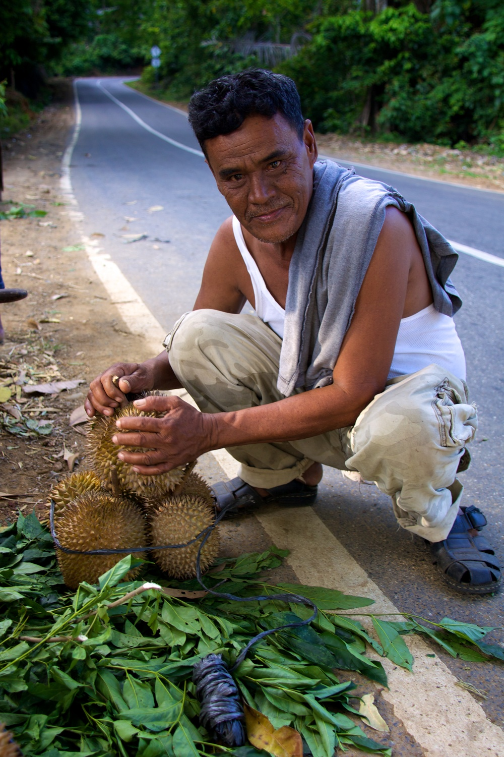 A man sells bundles of strong-smelling durian fruit along the mountainous stretch of road in Aceh, Indonesia. He sells a bundle (about five fruits) for 75,000 rupiah or approximately 8 US dollars. He says his lifestyle hasn't been changed at all by the USAID road.