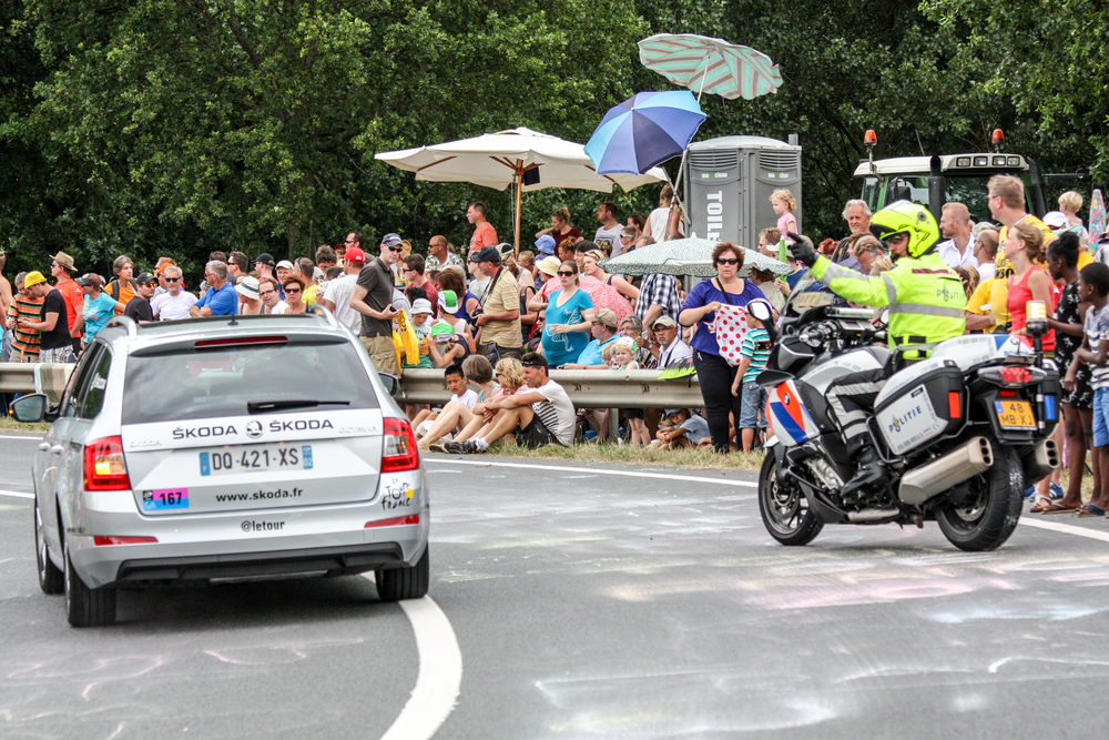 Before the riders pass by, there is some police presence to ensure the roadway is clear.  Prior to the riders there is a caravan of vehicles going by with their riders tossing souvenirs and free items from race sponsors.