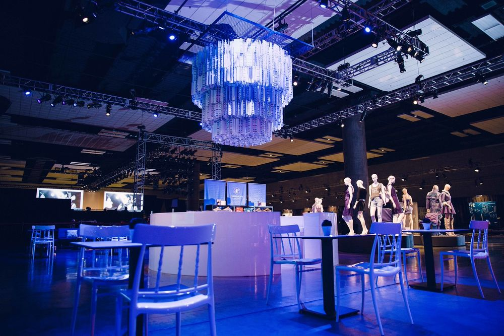 The chandelier was illuminated in gradient hues of purples and blues, and positioned over a circular acrylic bar.