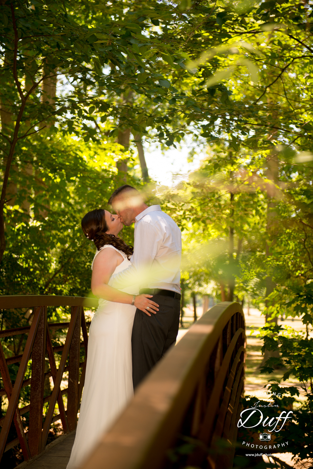 Firefighter Park Wedding - Troy MI wedding photographer. bride and groom kissing on a bridge voyeur.