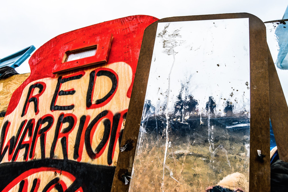 Mirror Shield conceived by Cannupahanska Luger Photo by Rob Wilson Photography taken at Standing Rock on Thanksgiving Day, Turtle Island police in reflection.png