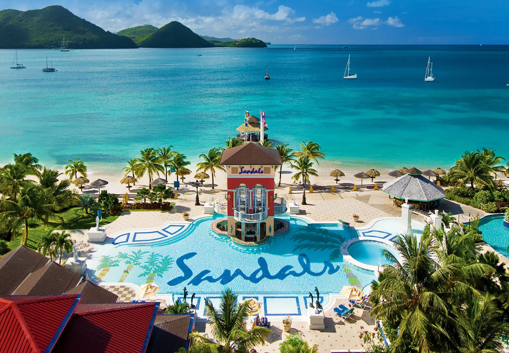 """Ideally located on its very own peninsula, Sandals Grande St. Lucian is often described as the """"closest vacation to a picture-perfect postcard."""" Cradled to the west by Rodney Bay - boasting the calmest waters in all of Saint Lucia - and to the east by the majestic Atlantic Ocean, this magnificent resort showcases awe-inspiring panoramic views that will linger in your heart forever. Volcanic mountains draped in blankets of green rise majestically from an impossibly clear blue sea. A sheltered mile-long beach extends an open invitation for days of endless water play. This is paradise as it was meant to be, full of natural beauty, rich in history, and resplendent in pure romance."""
