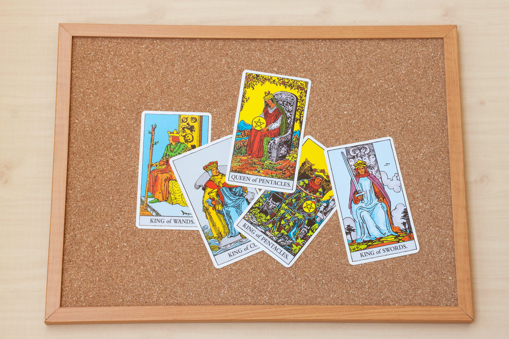 Tarot court cards on the cork board. Queen and King cards.