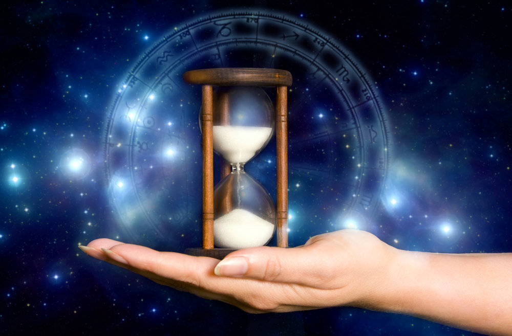 female hand holding an hourglass over blue mystical background with stars and astrology chart
