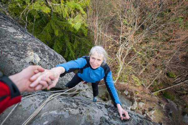 Male-rockclimber-is-helping-a-climber-female-to-reach-a-peak-of-mountain.jpg