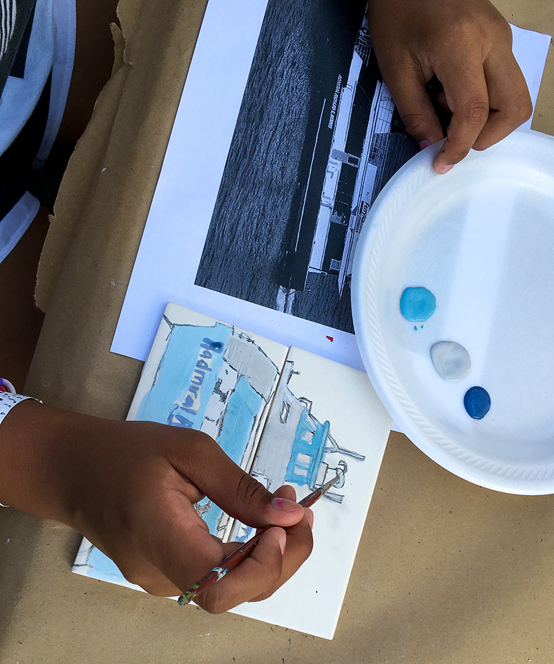 Participant painting a tile of a ship in the Community Tile Project