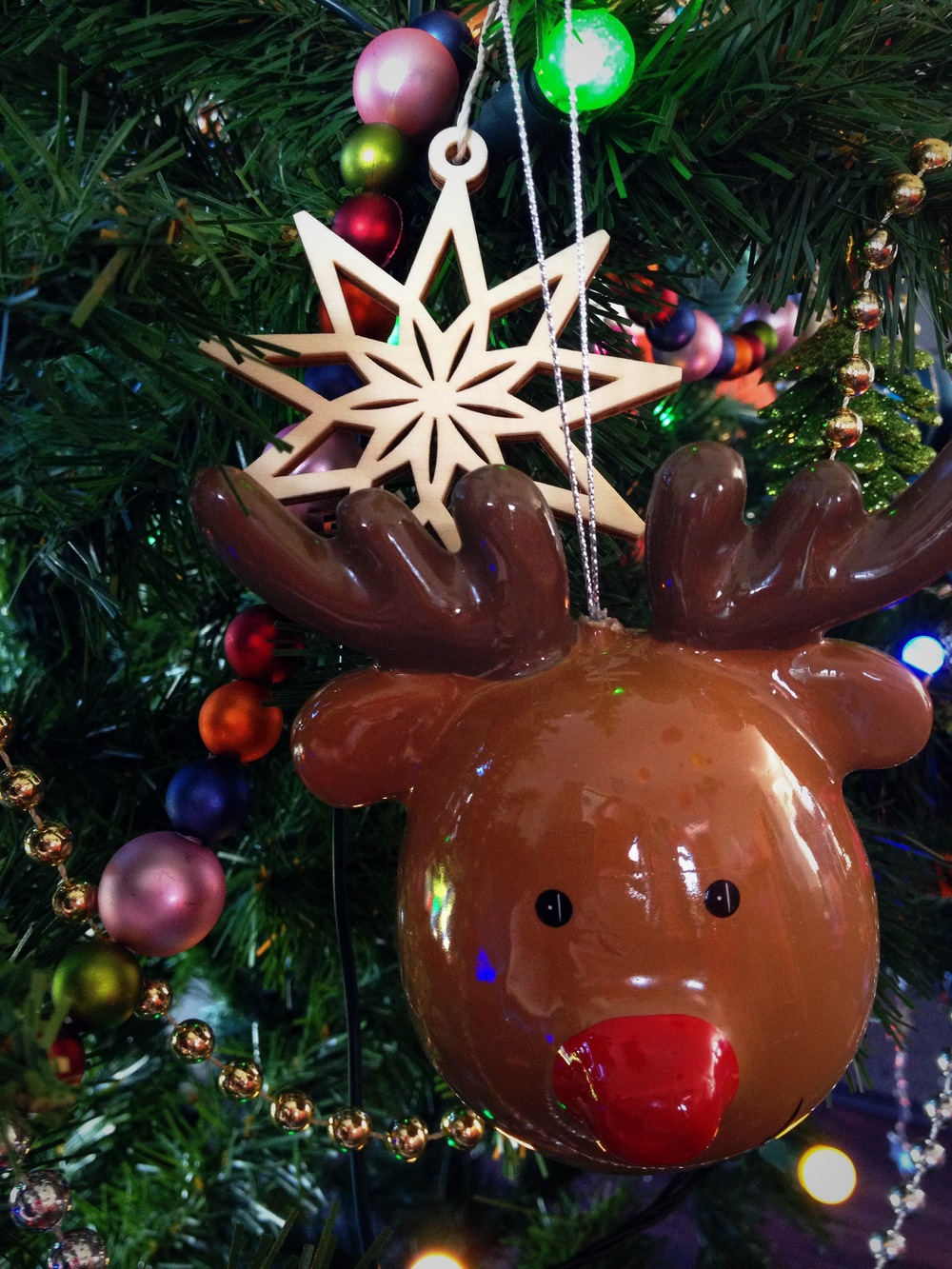 A Scandi precision cut wooden snowflake, next to a plastic Rudolph. Anarchy!