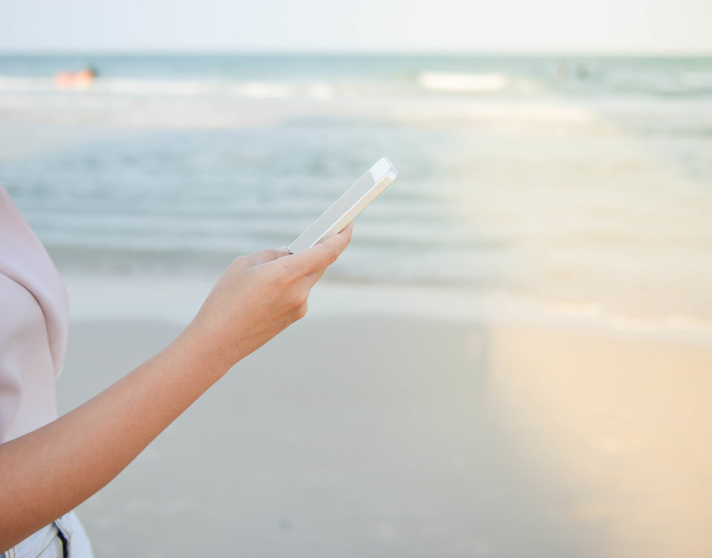 Woman is playing the mobile phone at the beach in the weekend