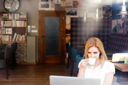 Blond woman with notebook in cafe drinking coffee