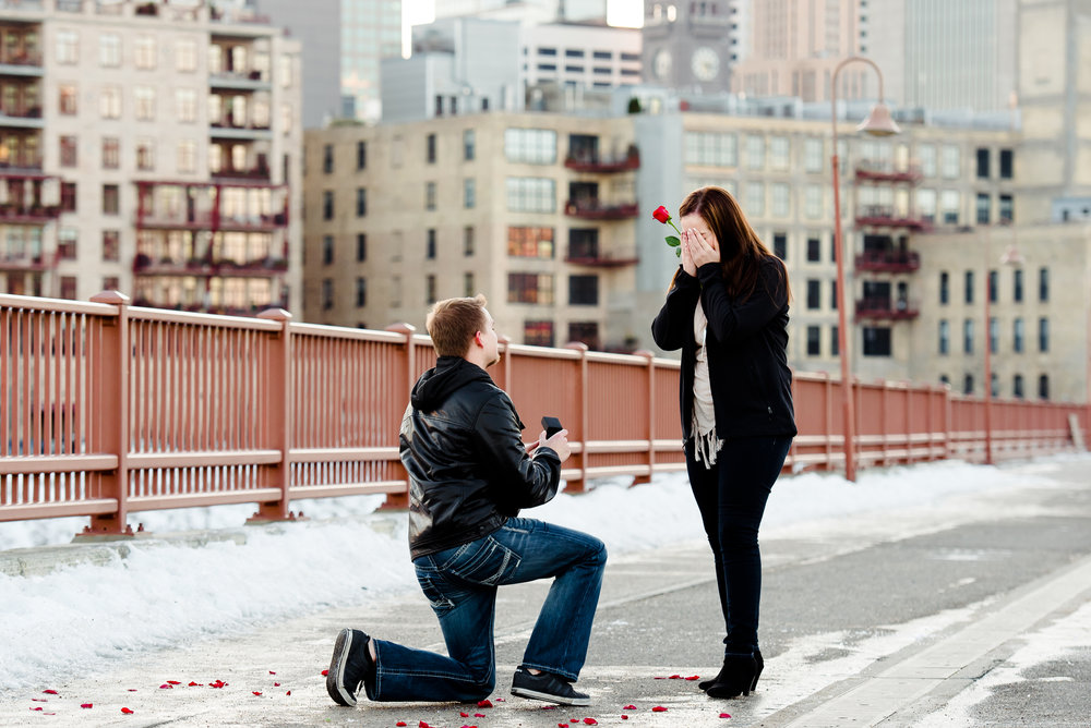 My Fiancé did an amazing job with the proposal! Our first date included a couple hour walk around a city, with beautiful lights and gorgeous views, as we talked and walked hand in hand. He wanted to recreate this, so he surprised me with a nice walk through Minneapolis and on the stone arch bridge, where he had Laura Robinson Photography secretly awaiting our arrival, with roses and candles set up in the perfect spot. We walked hand in hand along the bridge, enjoying the view, and as we approached the flower display, he talked about how this reminded him of our first date... He gave the most adorable speech and got down on one knee and asked! I obviously said YES! and she caught all of it on camera! We absolutely love our photos, and can't thank her enough for capturing our special day!