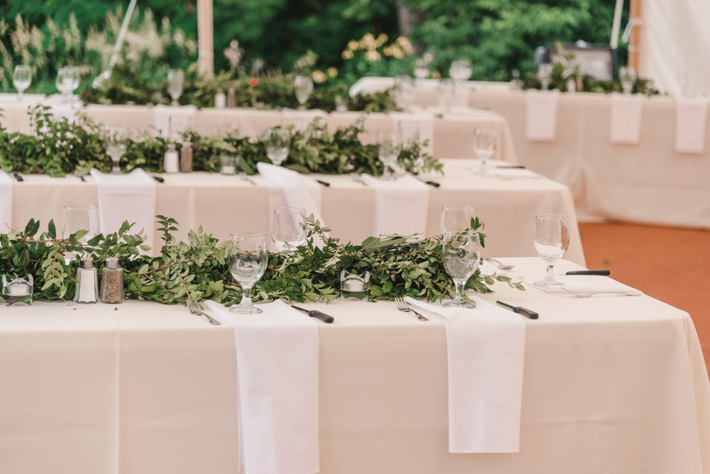 Fresh, lush green table garlands at wedding reception