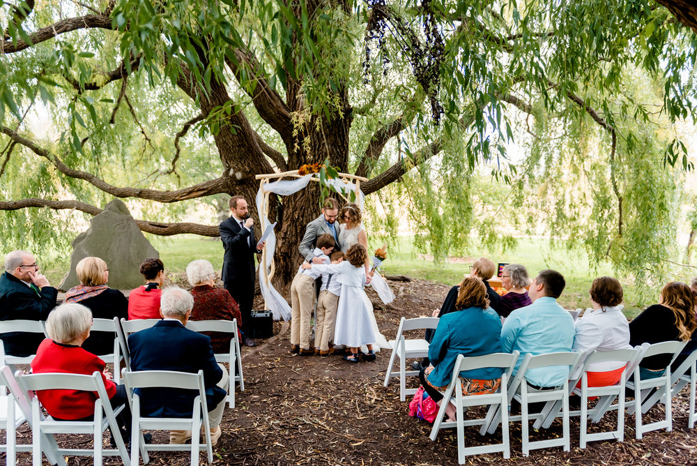 Ceremony Kiss at Weeping Willow Trees Ceremony Site at MN Landscape Arboretum - Fall Wedding - Minneapolis area Wedding Photographer
