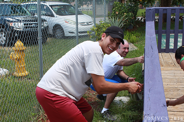Juan Muñoz and Rodolfo Rodriguez paint a fence