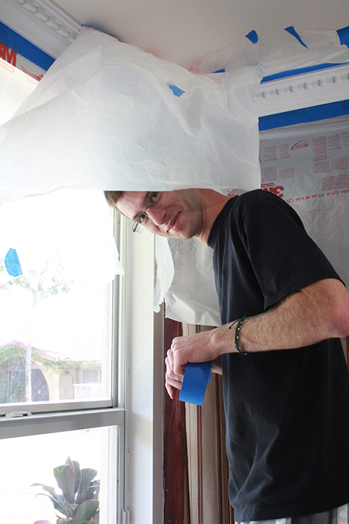Pre-theologian Thomas Coppola helps to tape a room for painting