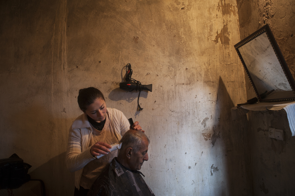 A displaced Syrian-Armenian gets his hair cut at a local's home turned makeshift barber shop.