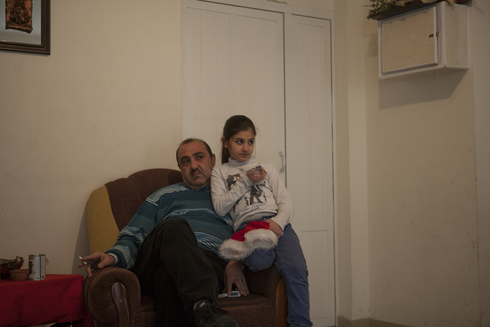 Many Syrian-Armenians fled to Yerevan - Armenia's capital. A father and daughter sit together in an apartment donated by the Catholic Church for the most desperate.