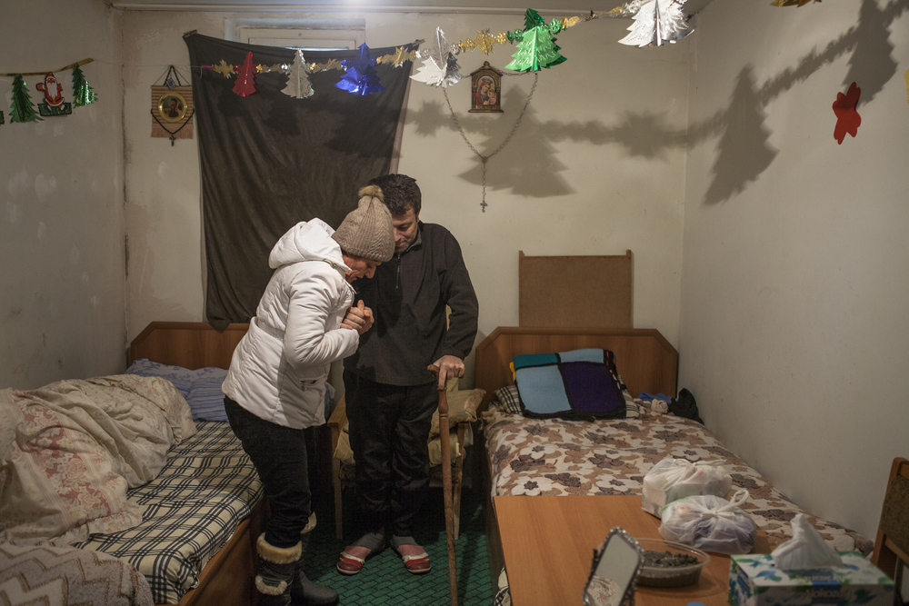 A displaced Syrian-Armenian helps her bedridden adult son walk to the bathroom in a house provided by the Catholic Church for Syrian-Armenians with the most need for assistance.