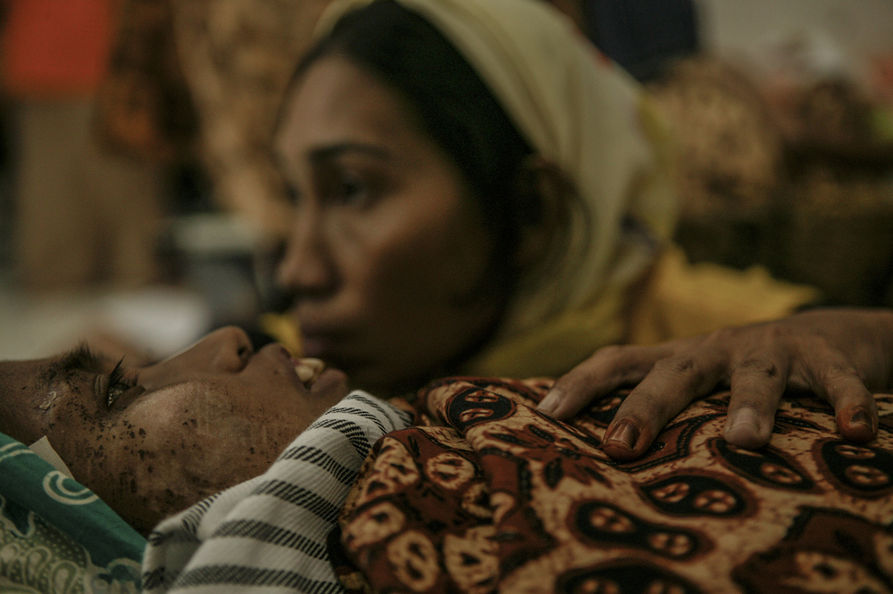 An injured woman comforted by her sister at a hospital.
