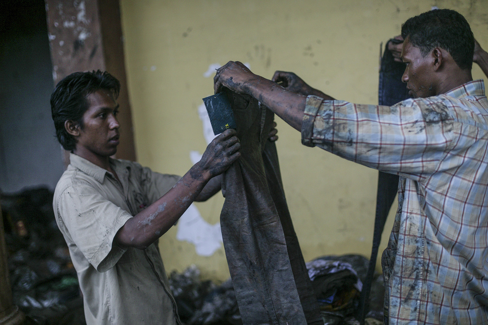 Locals salvage items found in the rubble of mud and debris in a shopping district of Banda Aceh.