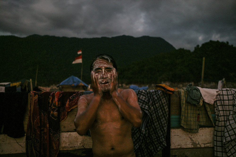 A man washes at dusk - at a camp for survivors.
