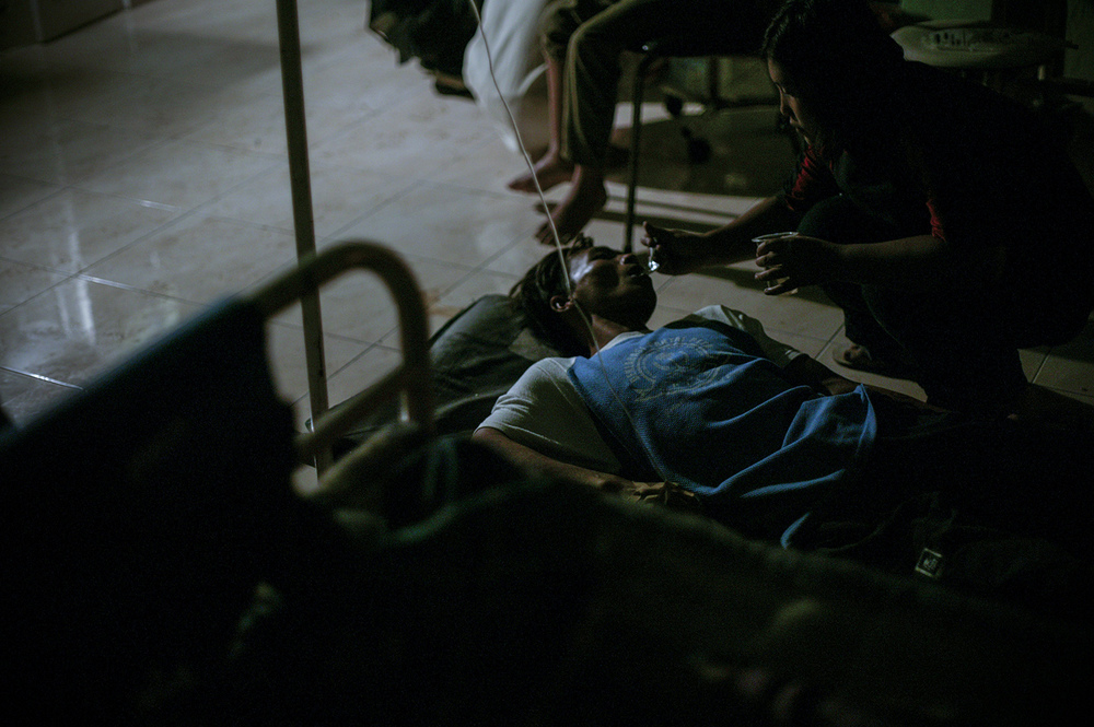 An injured man being fed by a family member at the hospital.